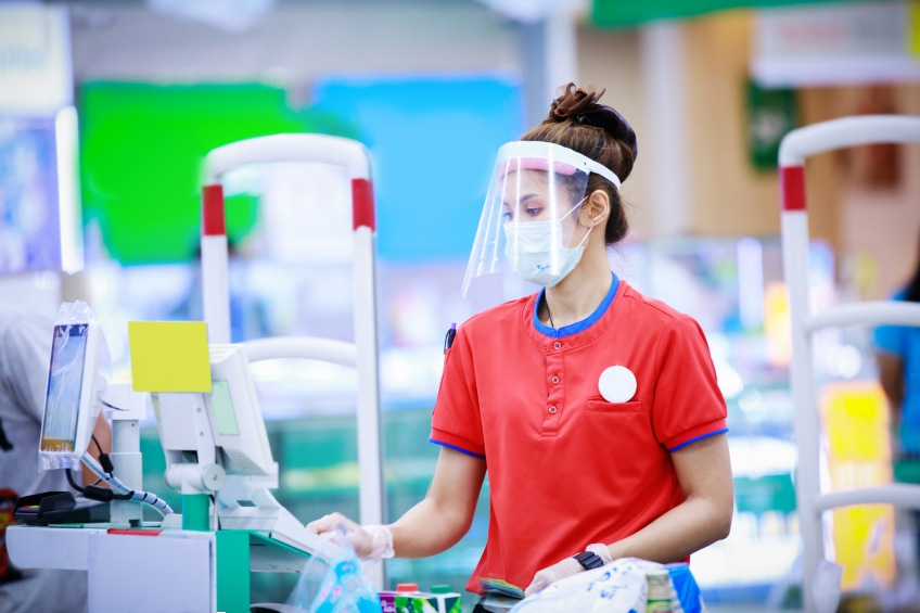 worker with face shield in supermarket