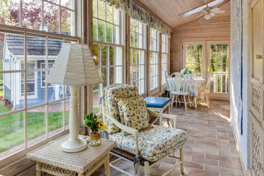 sunroom with natural light, floral furniture, wood walls, and brick floors